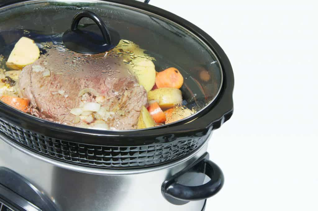 Illustrating is it safe to leave food in a crock pot overnight, with food cooking in a slow cooker